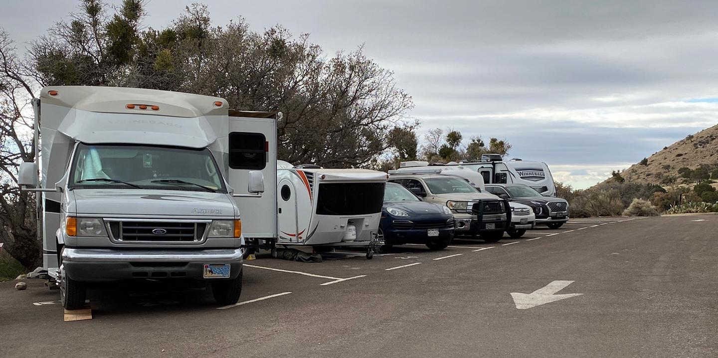 Row of RV campsite number 21-25.  Shown while occupied.  Campsite 24 is the second from the left of photo and shown with a small camper trailer and small vehicle parked side by side.Row of RV campsite number 21-25.  Site 24 is the second from the left in the photo.