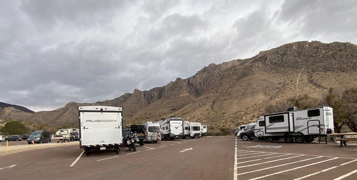 A view of RV campground parking area with sites 21-30 shown.  Site 27 is located along the left side of travel lane.  Mountain views in the background.A view of RV campground parking area with sites 21-30 shown.  Site 27 is the second on the left.
