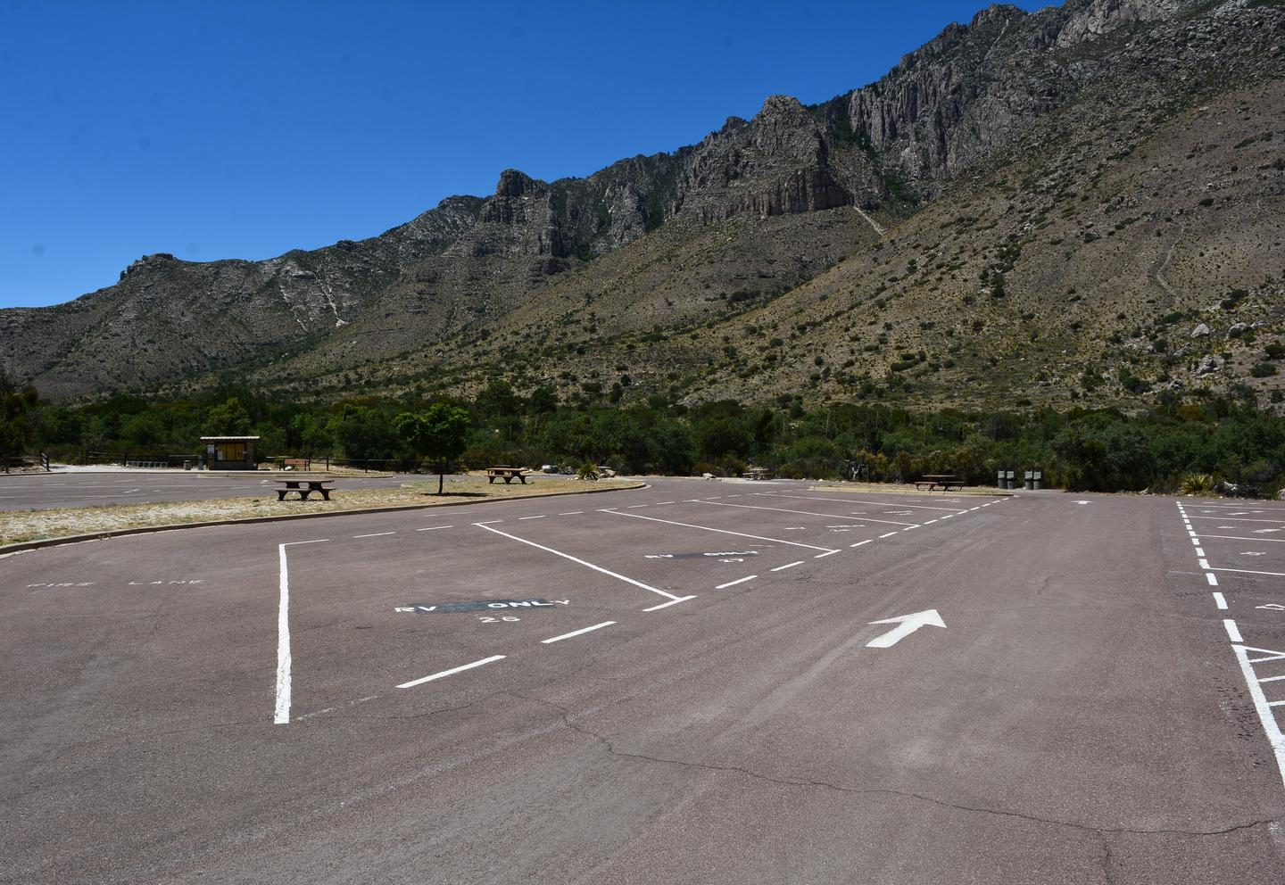 A view of RV campground parking area with sites 21-30 shown.  Site 28 is located along the left side of travel lane.  Mountain views in the background.A view of RV campground parking area with sites 21-30 shown.  Site 28 is located along the left side of travel lane.