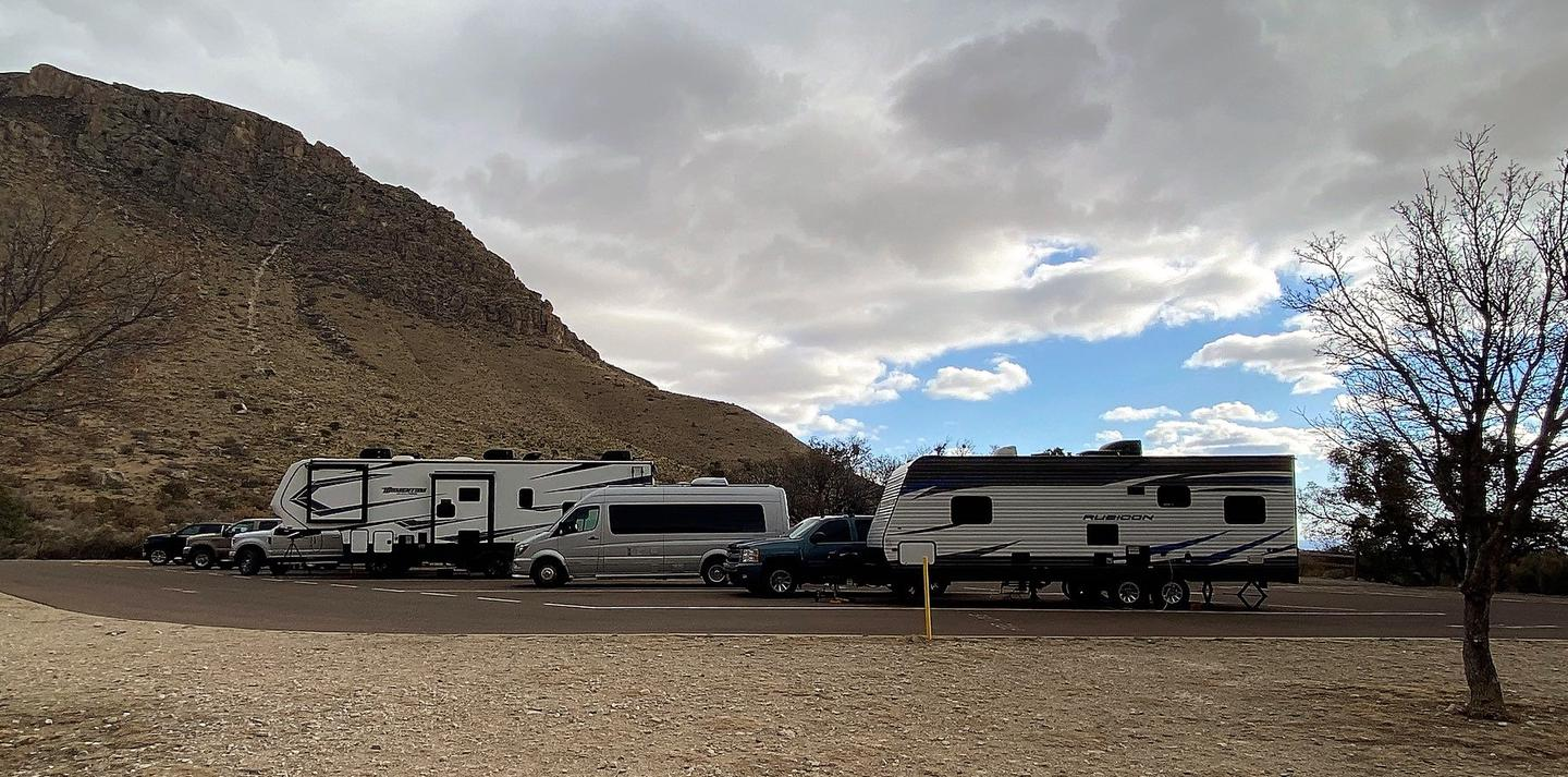 The row of RV campsites number 26-30.  The sites are occupied in this photo by RVs, camper trailers and camper vans.The row of RV campsites number 26-30.