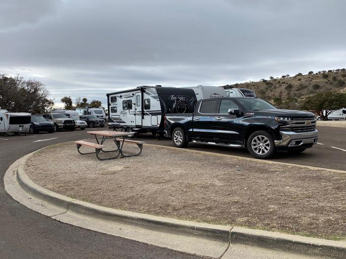View of RV Site 30.  In the foreground is small area with a picnic table adjacent to the site.  The site is occupied by a camper trailer and truck.RV Campsite number 30.  This site offers a small area with a picnic table adjacent to the site.