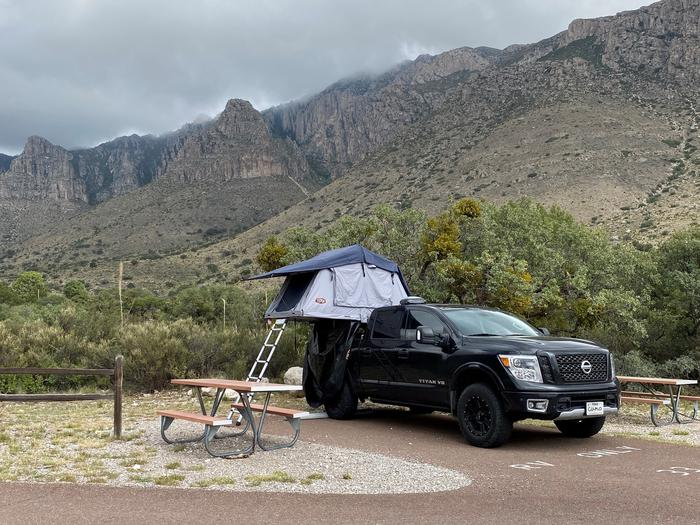 RV Site 33 shown with a pickup truck and vehicle mounted tent on back.  There is a picnic table to the left of the spur and mountain views to the back.RV Site 33 is a paved, pull-in site.  The paved spur is short and restricts vehicle size.