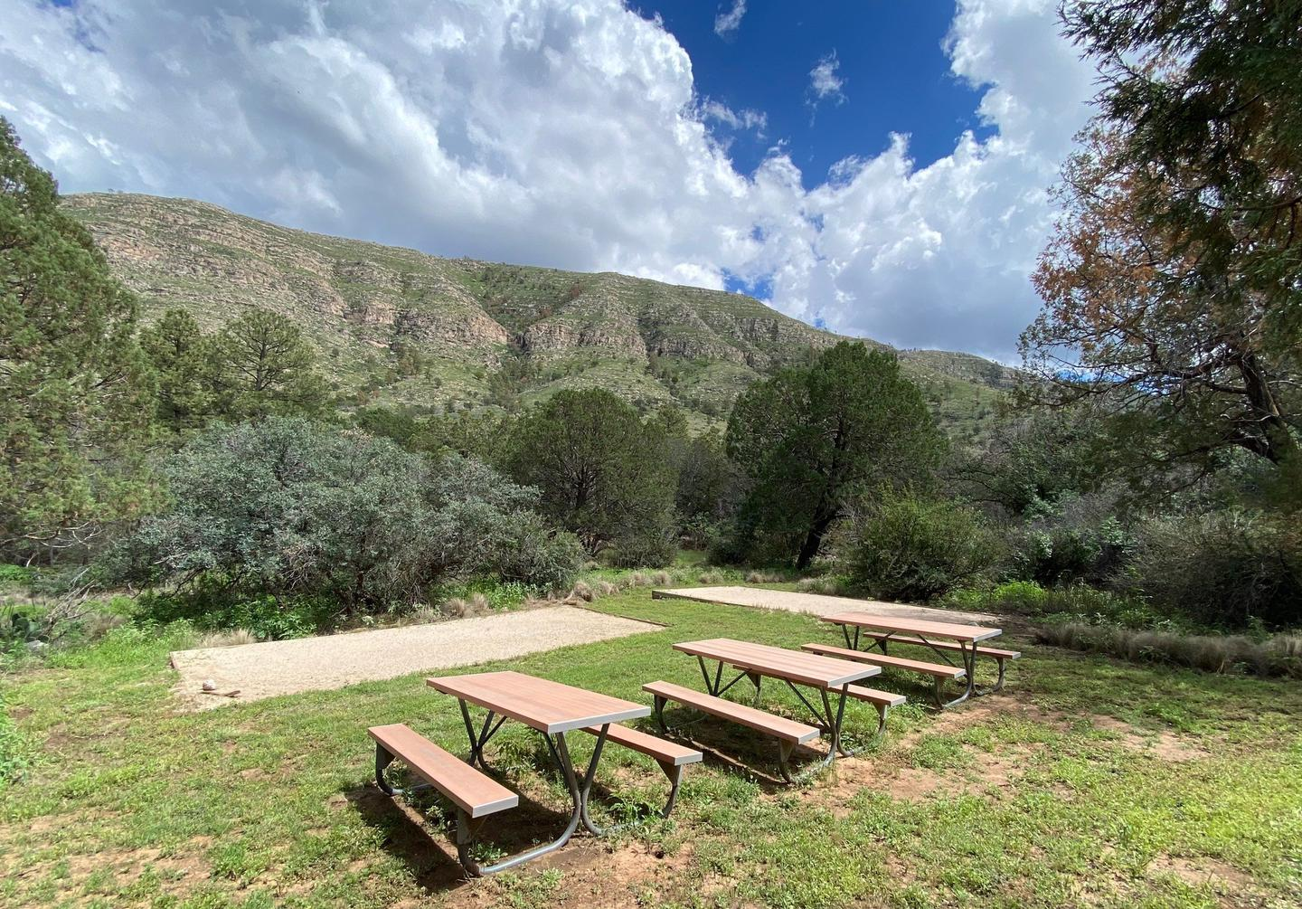 Dog Canyon Group Campsite with two tent pads delineated with landscape timbers and filled with fine crushed gravel. Three picnic tables are located in an open grassy area for groups to gather.Dog Canyon group campsite with two tent pads and three picnic tables.