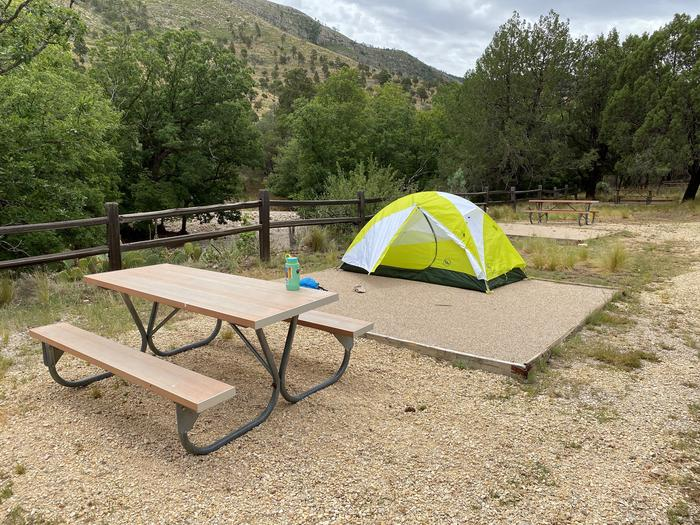 Tent campsite #3 with a two-person tent displayed on the tent pad and room to spare.  The site has a picnic table and offers views of the mountains.Tent campsite #3 with a two-person tent displayed on the tent pad.