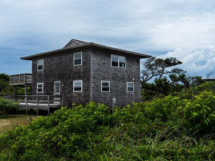 2-story house set behind lush greenery.Bayberry Dunes Beach House