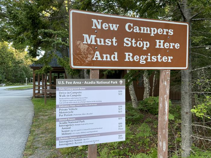 Signs stating- New campers must stop here and register, as well as a sign with pricing for camping and park passesSigns for new camper information and park pass description.
