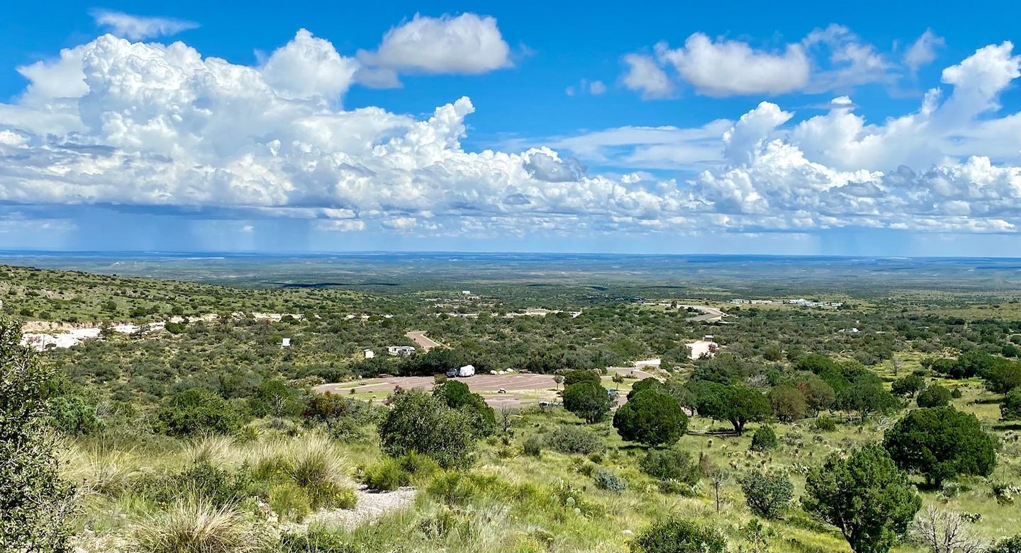 View of Pine Springs Campground as seen from the Guadalupe Peak trail.  Campground and trailhead parking area surrounded by desert vegetation. View of Pine Springs Campground as seen from the Guadalupe Peak trail with views of the Permian Basin in the distance.