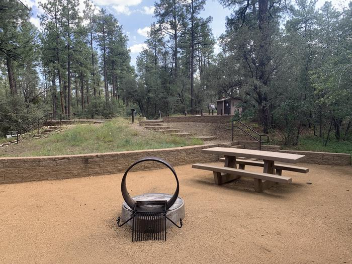 Site H34. View from campsite up to parking on street. In view are fire pit, picnic table with vault latrine in background.  A dozen steps are visible leading up to parking area.