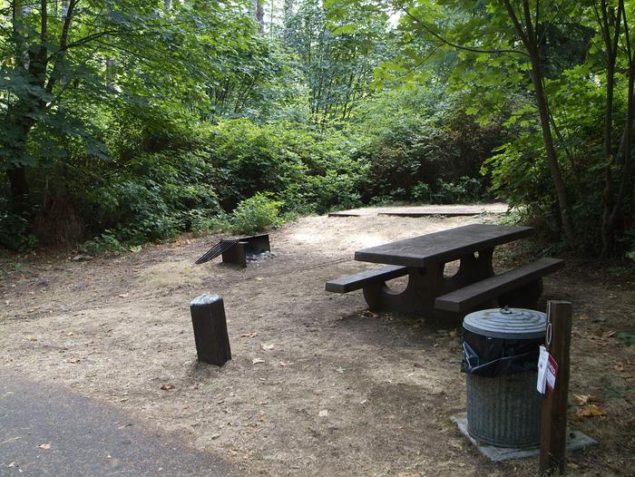 Camp site 10: small site with fire ring, table, and tent pad. Parking is parallel to site and campground road.