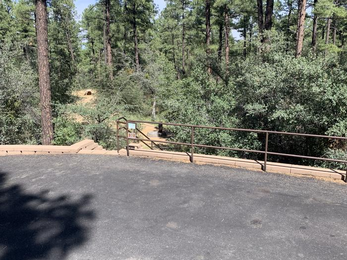 A photo of Site 32 of Loop H at LYNX CAMPGROUND with Fire Pit, guard rail, that leads to a dozen steps down to campsite. (The picnic table in deep background is site H33).