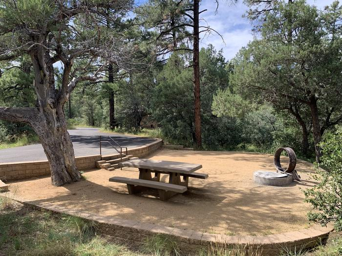 A photo of Site 23 of Loop E at LYNX CAMPGROUND with Picnic Table, Fire Pit.  Flush toilet house is slightly visible in background.