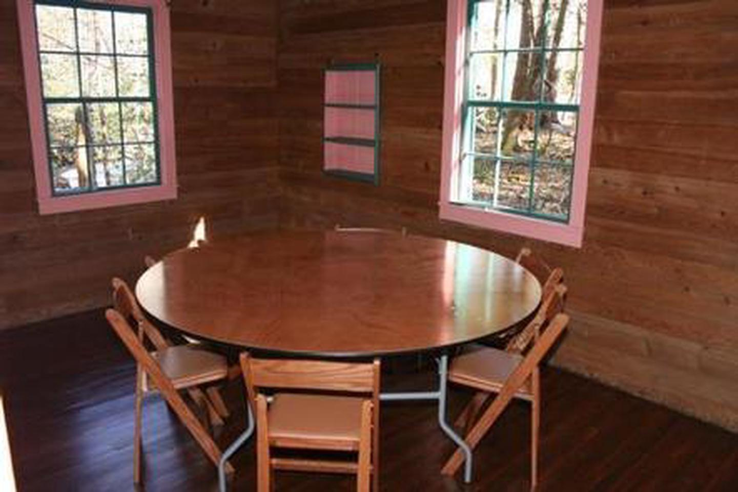 Small room located in Spence CabinSmall room showing table and chairs with window views