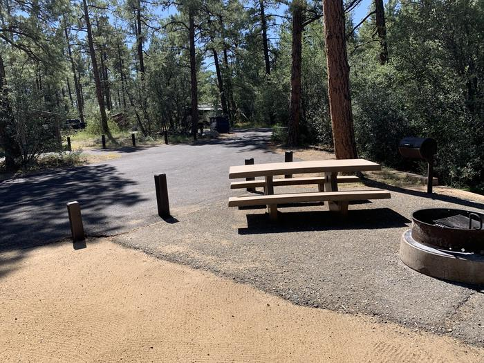 A photo of Site 35 of Loop H at LYNX CAMPGROUND with Picnic Table, Fire Pit, and grill. View is from campsite into H Loop with partial view of vault latrine.