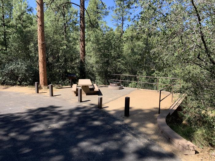 A photo of Site 35 of Loop H at LYNX CAMPGROUND with Picnic Table, Fire Pit, and grill. View shows on-street parallel parking along campsite.