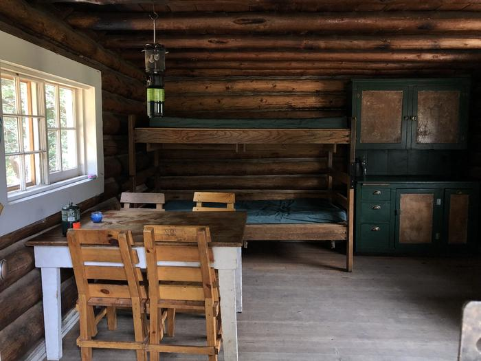 Cabin interior - two bunked beds, table with chairs, cabinetCabin interior - two beds downstairs and two more in the loft.