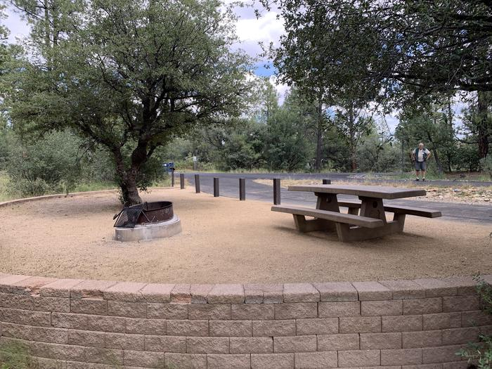 A photo of Site 01 of Loop A at LYNX CAMPGROUND with Picnic Table, Fire Pit. View is through campsite back toward campground. Dumpster is in background.