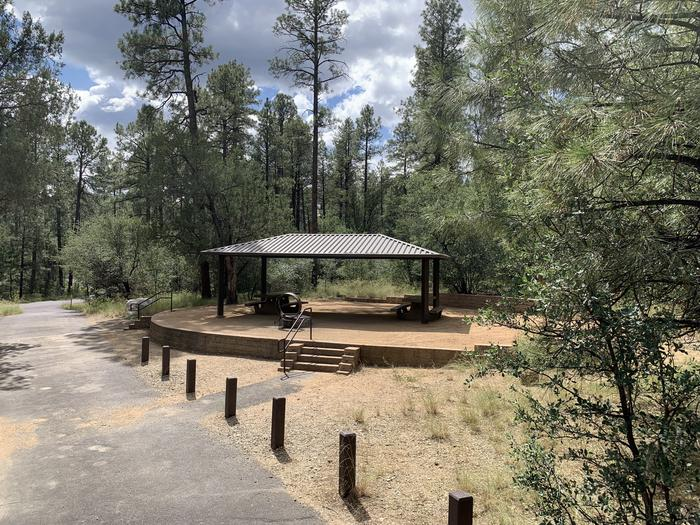 A photo of Site 19 of Loop D at LYNX CAMPGROUND with 2 Picnic Tables, Fire Pit, Shade with long pull through driveway. 5 stairs to campsite.