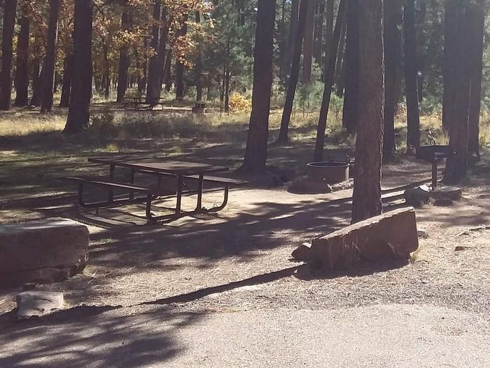 Site 18 with two large rocks, picnic table and campfire ring.Campsite 18 has a campfire ring and table.