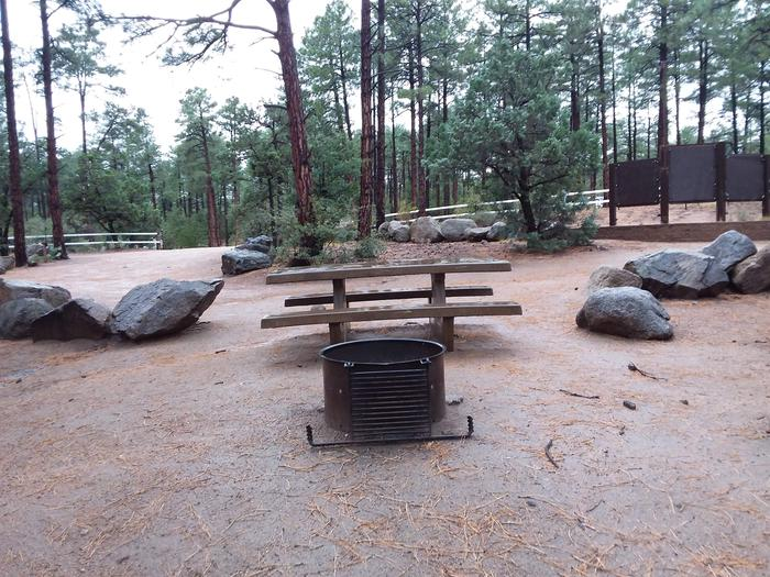 Site 1 campfire ring with a grill, and table with rocks on either side.Campsite 1