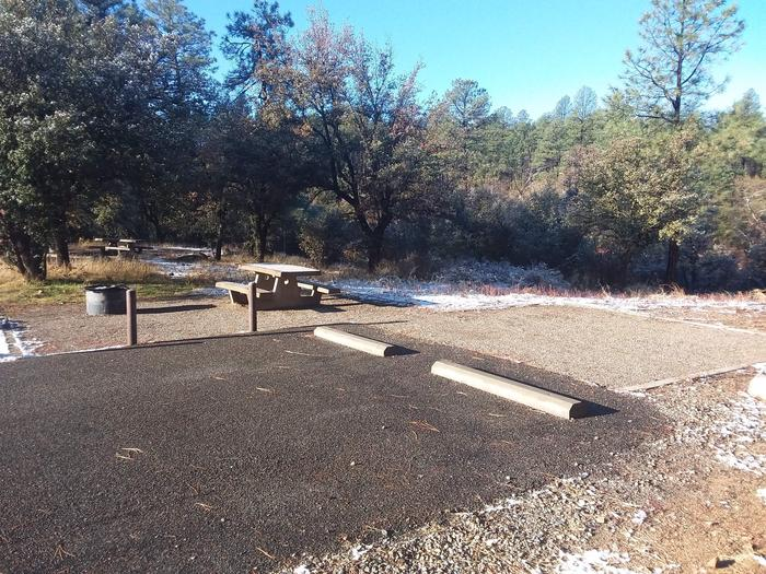 Campsite 03 with parking spaces, a picnic table, fire pit and an open surface for tent placement