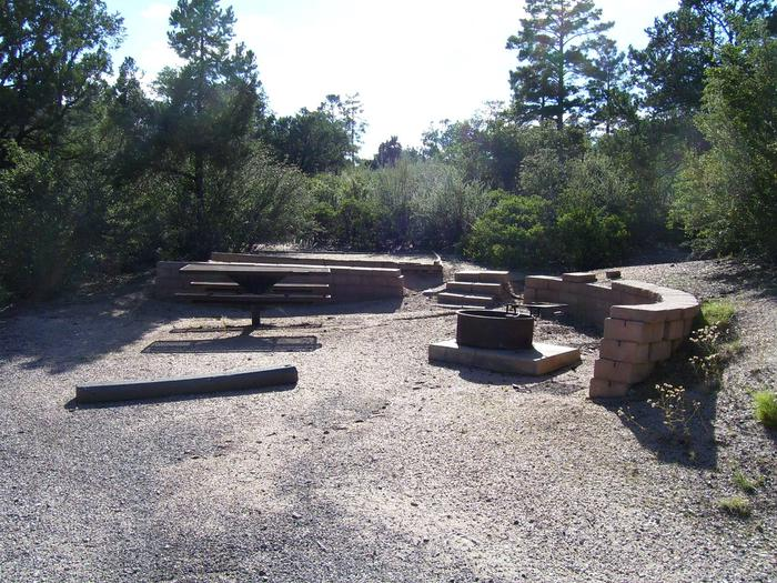 Yavapai Campsite 19 with a picnic table and fire ring as well as a designated space for tent placement behind the brick wall
