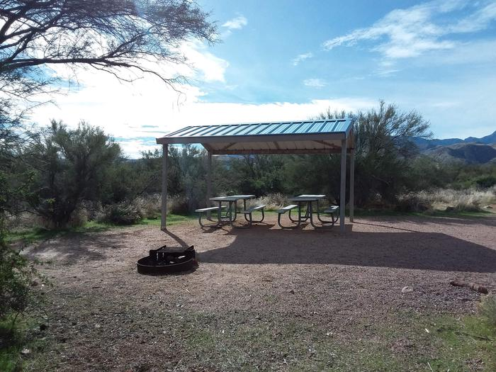 Site 4 with picnic tables, a fire ring, shade structure, and parking.