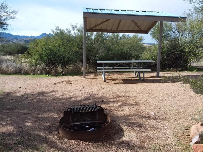 Site 5 with a picnic table, fire ring, shade structure, and parking.
