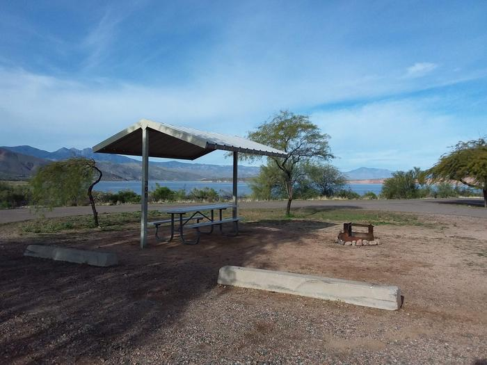 Windy Hill Campground Coyote Site 300: shade structure, table, fire pit and view of the lakeWindy Hill Campground Coyote Site 300