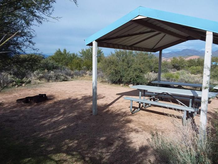 Site 12 with  picnic tables, a fire ring, shade structure, and parking.Site 12 with a picnic table, fire ring, shade structure, and parking.