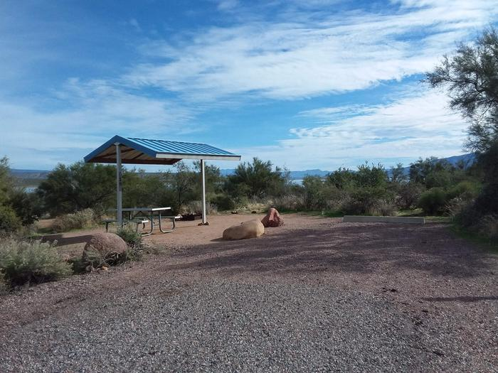 Campsite 19 at Cholla Campground with a picnic table, fire ring, shade structure, and parking.