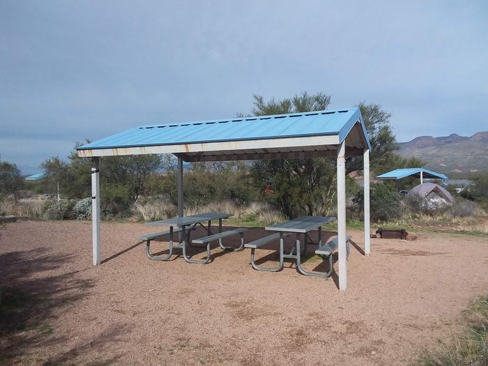 Site 24 with picnic tables, a fire ring, shade structure, and parking.