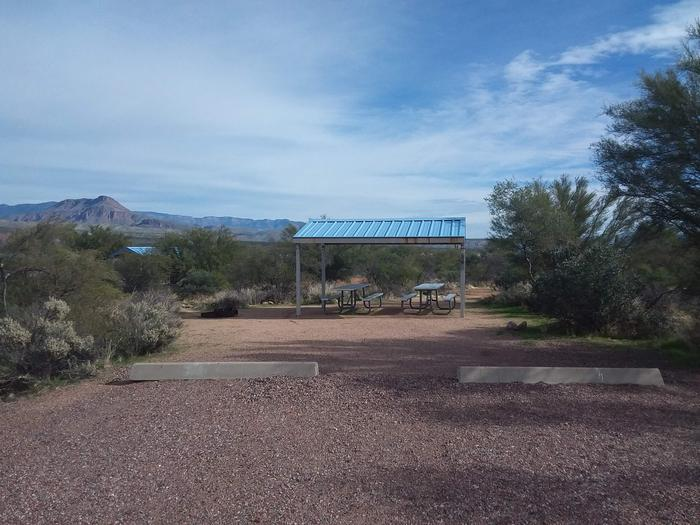 Site 26 with picnic tables, a fire ring, shade structure, and parking.