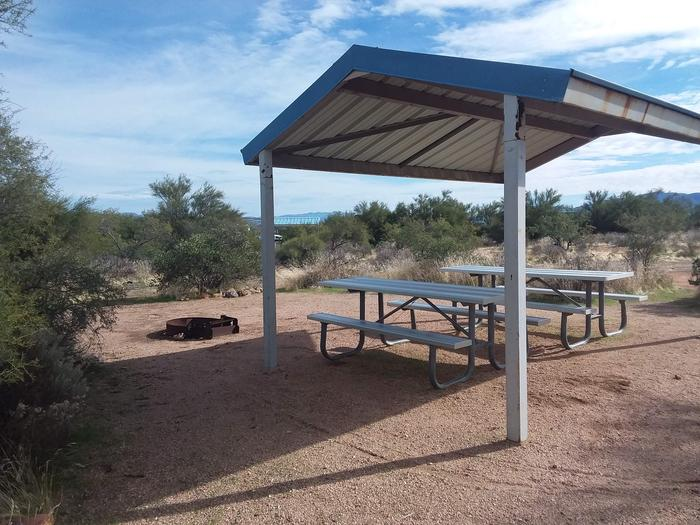 Campsite 27 at Cholla Campground with picnic tables, a fire ring, shade structure, and parking.