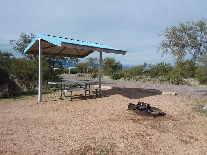 Site 34 with a picnic table, fire ring, shade structure, and parking.