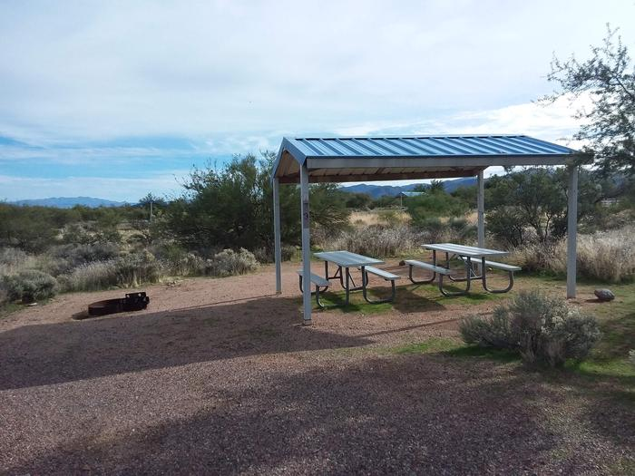 Campsite 73 at Cholla Campground with picnic tables, a fire ring, shade structure, and parking.