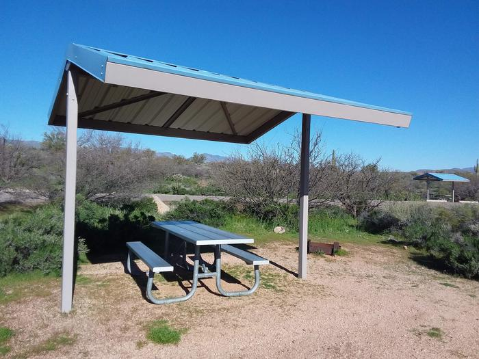 Site 76 with a picnic table, fire ring, shade structure, and parking.