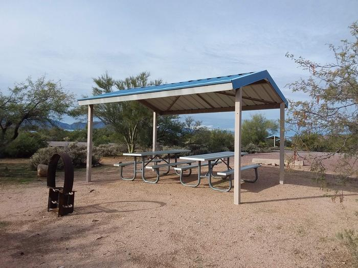 Campsite 83 at Cholla Campground with picnic tables, a fire ring, shade structure, and parking.