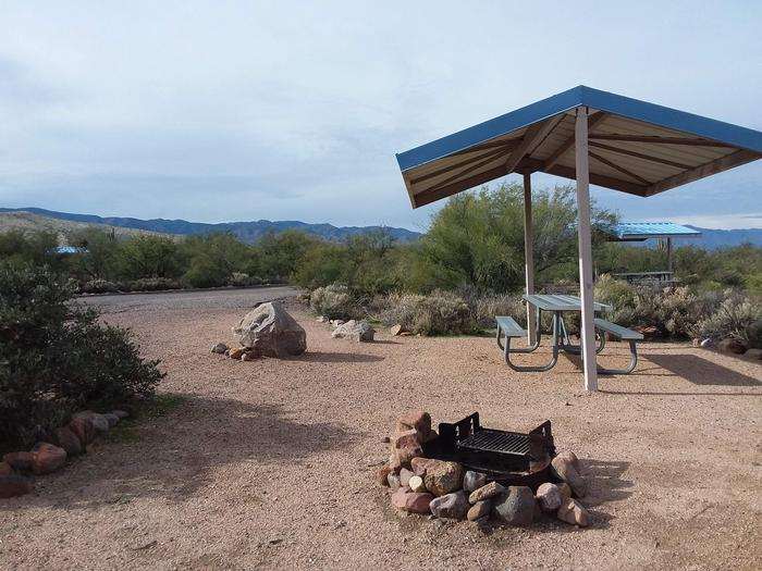 Site 86 with a picnic table, fire ring, shade structure, and parking.