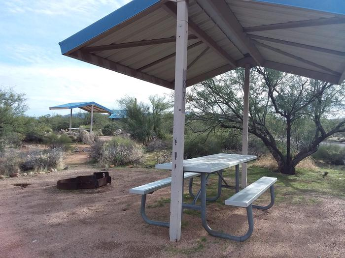 Campsite 87 at Cholla Campground with a picnic table, fire ring, shade structure, and parking.