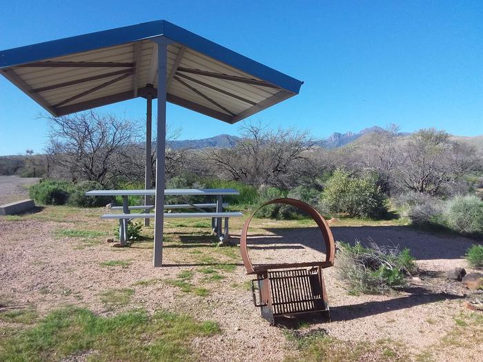 Site 94 with a picnic table, fire ring, shade structure, and parking.