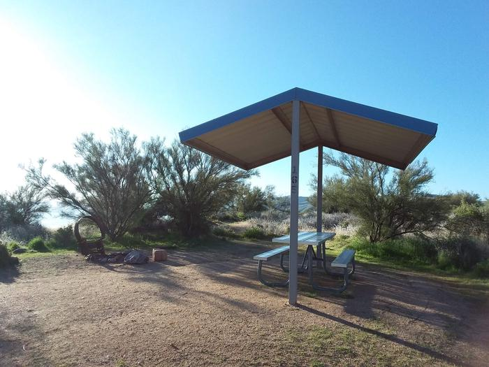 Site 165 with a picnic table, fire ring, shade structure, and parking.