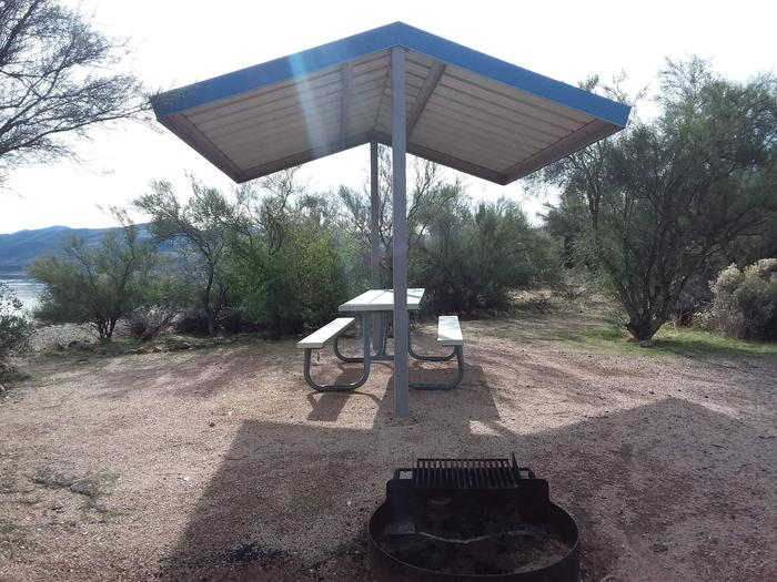 Site 174 with a picnic table, fire ring, shade structure, and parking.