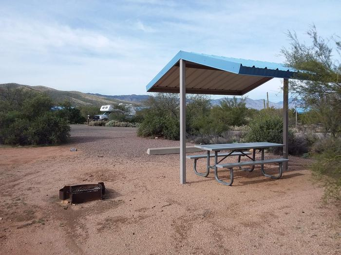 Site 180 with a picnic table, fire ring, shade structure, and parking.