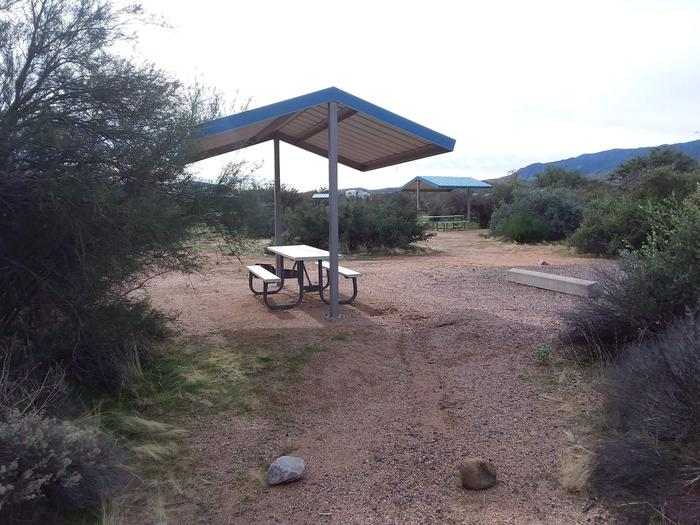 Site 180 with a picnic table, fire ring, shade structure, and parkingSite 180 with a picnic table, fire ring, shade structure, and parking.