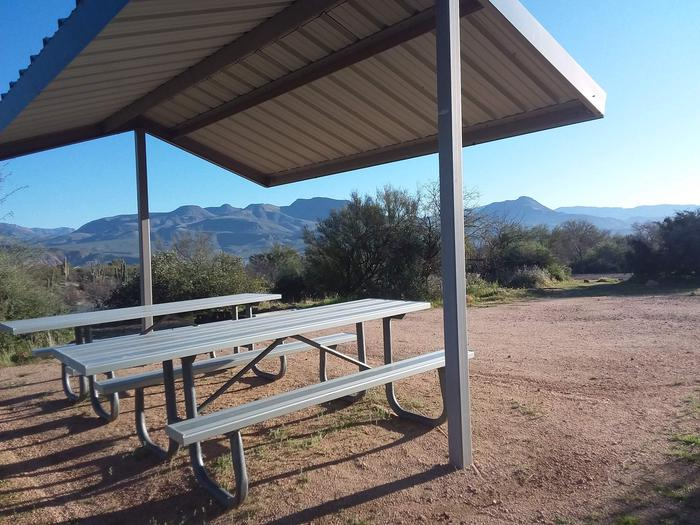 Site 183 with picnic tables, a fire ring, shade structure, and parking.