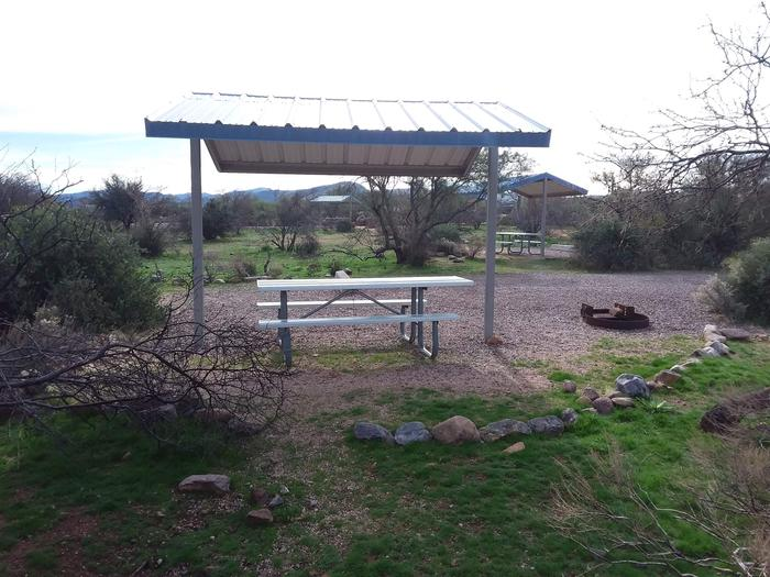 Site 184 with a picnic table, fire ring, shade structure, and parking.