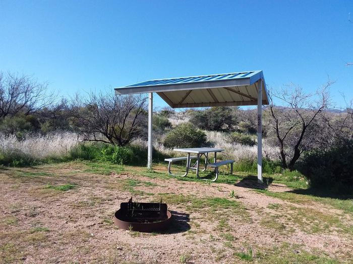 Site T12 with a picnic table, fire ring, shade structure, and parkingSite T12 with a picnic table, fire ring, shade structure, and parking.