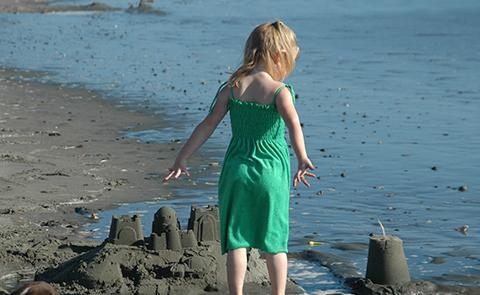 SandcastlesYoung girl builds sandcastles on the edge of Olympic Coast National Marine Sanctuary