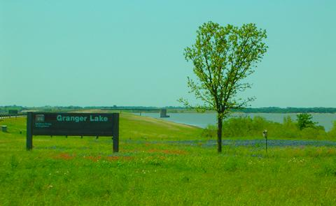 Granger main sign in a field of flowersDam and flowers at Granger