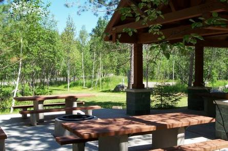 Picture of group site picnic shelter and tables.Group site shelter and tables.  Group sites also include electrical hook-ups, designated parking areas, tent pads, access to the lake, and fire rings.